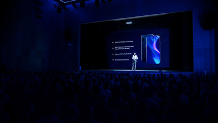Live Event with Brand New Products Reveal: Keynote Speaker Presents Smartphone Device to Audience. Movie Theater Screen Shows Mock-up Touch Screen Phone with High-Tech Features and Top Highlights