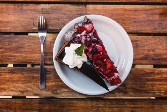 Torta de chocolate con frutos rojos y crema sobre un plato blanco y mesa de madera