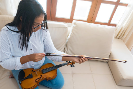 A young African woman playing the violin at home