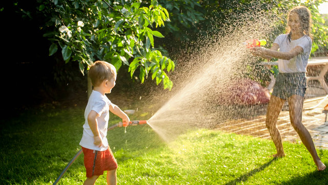 Litle boy having water fight on the backyard with his sister