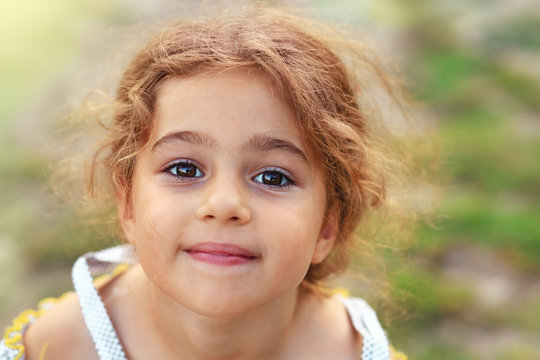 Portrait of smiling cute little girl at green of summer park. Happy child looking at the camera