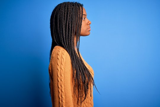 Young african american woman wearing casual yellow sweater standing over blue isolated background looking to side, relax profile pose with natural face with confident smile.