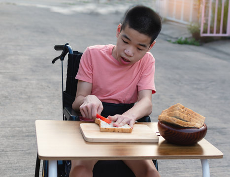Disabled child on wheelchair is interested in skills development cooking food on home background, Special child lifestyle, Life in the education age of special need kids, Happy disability kid concept.