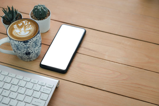 Mock up on Mobile phone screen and hot art cappuccino coffee beside wireless keyboard on a wooden table, Space for putting advertising messages or product presentations