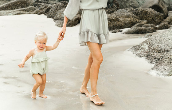 A small child, a girl with blond hair, walks along the sandy beach with her mother with beautiful slender legs.
