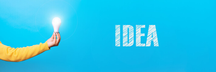 Wall Mural - hand holding light bulb, illuminated light bulb, panoramic image with inscription idea over blue background