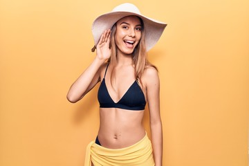 Young beautiful girl wearing bikini and hat smiling with hand over ear listening and hearing to rumor or gossip. deafness concept.