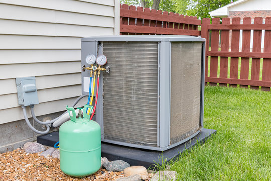 Dirty air conditioning unit. Condenser coils full of dirt and grass debris. Freon charging tools. Concept of home air conditioner repair, service, cleaning and maintenance