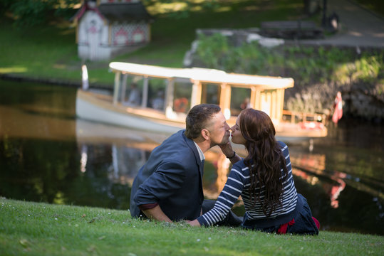 Man And Woman Kissing While Sitting On Grassy Field