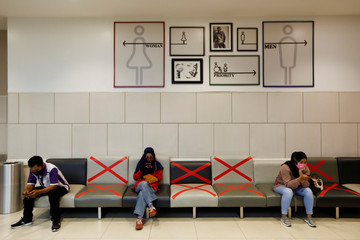 People wearing face masks use their phones and while sitting inside a shopping mall in Tangerang, on the outskirts of Jakarta