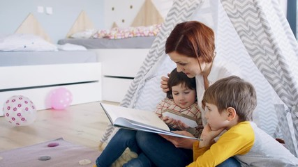 Wall Mural - Mother with small children in bedroom at home, reading story book.
