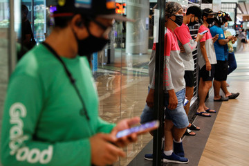 Food delivery riders queue up for their orders at a shopping mall, amid the coronavirus disease (COVID-19) outbreak in Singapore