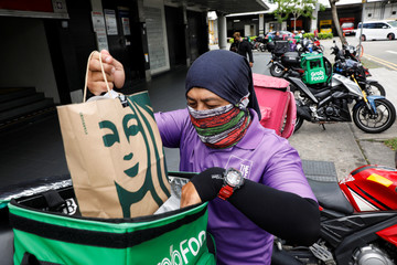 A food delivery rider gets ready for a delivery outside a shopping mall, amid the coronavirus disease (COVID-19) outbreak in Singapore