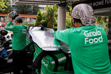 Food delivery riders get ready for a delivery outside a shopping mall, amid the coronavirus disease (COVID-19) outbreak in Singapore