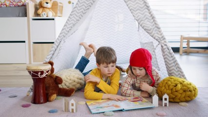 Wall Mural - Small children in bedroom indoors at home, reading book.
