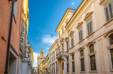Typical italian street with old colorful buildings and Torre della Pallata brick medieval tower background, Brescia city historical centre, blue cloudy sky, Lombardy, Northern Italy Fotomurales