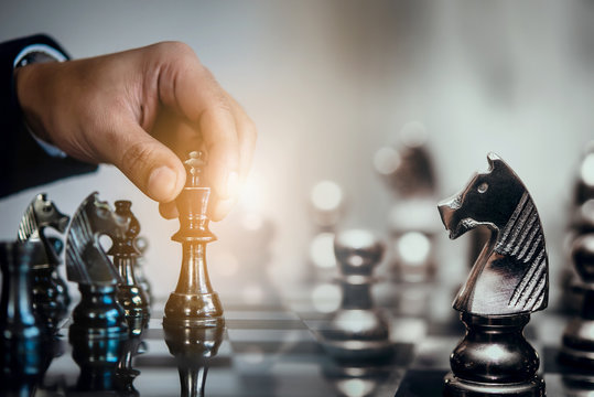 Businessman moving chess piece and think strategic to win game. Chess board game concept for ideas and competition and strategy, business success concept