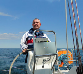 The captain at the wheel of a sailing yacht in calm seas, sunshine and blue skies. The man with the beard looks at the sea. He wears waterproof sailing clothing. Behind the man is a lifebuoy.