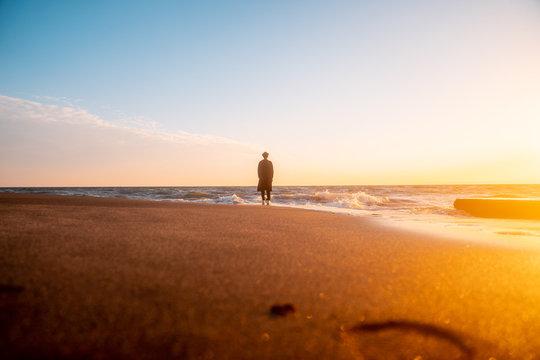 日本 神奈川県 鎌倉の七里ヶ浜の砂浜を夕方に歩く若い日本人男性と美しい夕陽