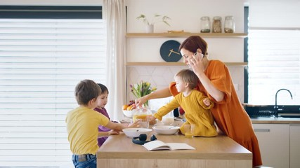 Wall Mural - Mother with small children and smartphone in kitchen in the morning at home, eating breakfast.