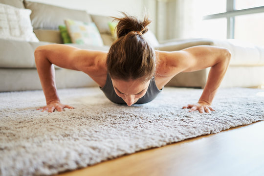 Woman working out at home. Pushups on the carpet. Looking down with bent arms