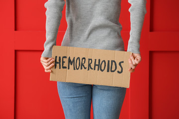 Autocollant pour porte Ane Young woman holding paper with text HEMORRHOIDS on color background