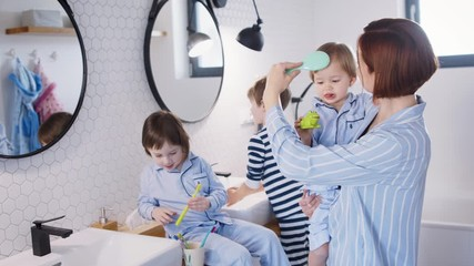 Wall Mural - Mother with small children in pajamas in bathroom at home, brushing teeth.