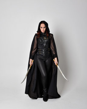 fantasy portrait of a woman with red hair wearing dark leather assassin costume with long black cloak. Full length standing pose holding a sword isolated against a studio background.