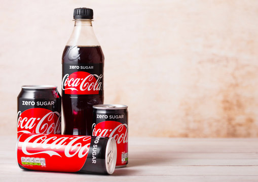LONDON, UK - AUGUST 03, 2018: Plastic bottle and aluminium tins of Zero Sugar Coca Cola soft drink on wooden background. Most popular drink in the world.