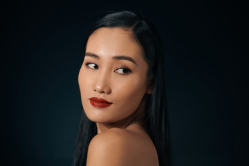 Portrait of attractive Asian woman isolated over balck background