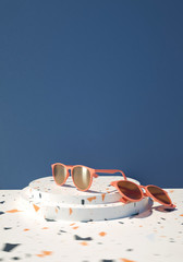 3d rendered illustration of pair of modern sunglasses presentation on blue background, copy space
