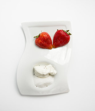beautiful strawberries on a white plate with sugar and sour cream view from above