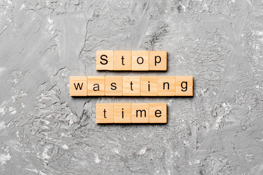 Stop wasting time word written on wood block. Stop wasting time text on cement table for your desing, Top view concept
