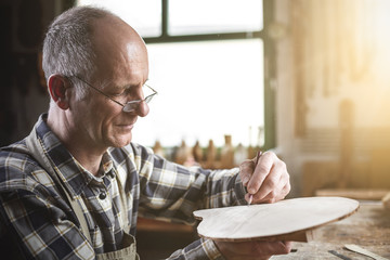 Mature carpenter marking a piece of wood with a pencil