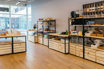 Zero waste shop interior details. Wooden shelves with different food goods and personal hygiene or cosmetics products in plastic free grocery store. Eco-friendly shopping at local small businesses. Wall mural
