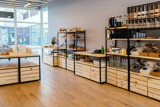 Zero waste shop interior details. Wooden shelves with different food goods and personal hygiene or cosmetics products in plastic free grocery store. Eco-friendly shopping at local small businesses.