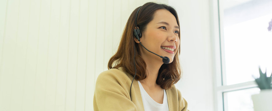 close up young call center employee woman wear headset to talking with colleagues and partner at desktop in living room for customer care and work from home concept