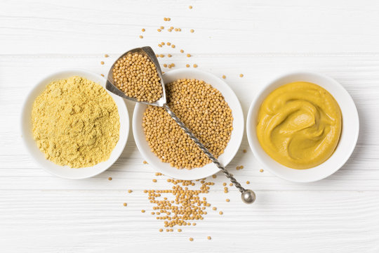 Set of yellow mustard sauce, powder and seeds in small bowls with silver spoon