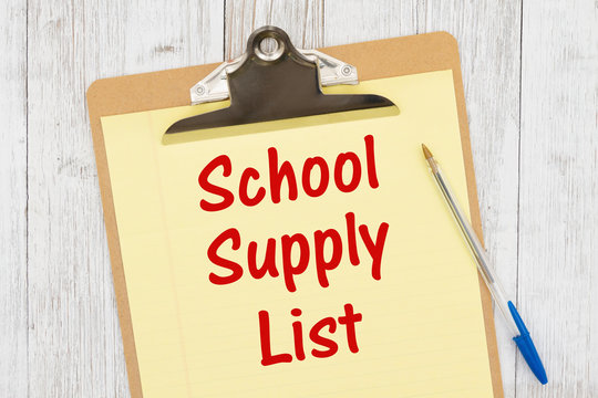 School supply List message on yellow lined paper with a pen on a clipboard