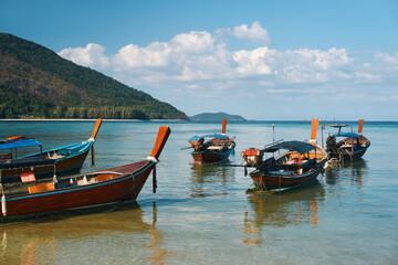 Long tail boats on tropical beach in Thailand