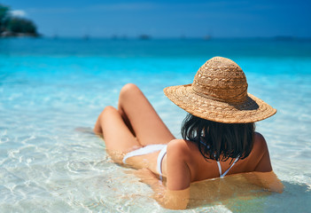 Back view of young woman in straw hat and white bikini relax in turquoise sea on tropical paradise beach