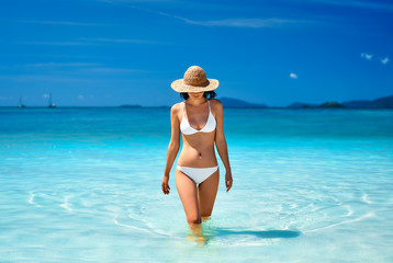 Sexy young woman in straw hat and white bikini on tropical paradise beach.