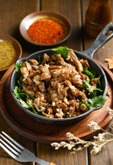 cumin fried lamb in pot on wooden table