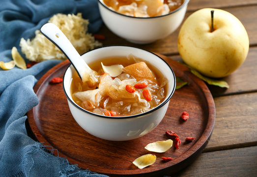 White fungus soup and pear in white bowl on wooden plate