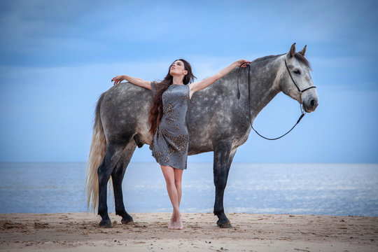 Beautyful woman walking on sea with horse
