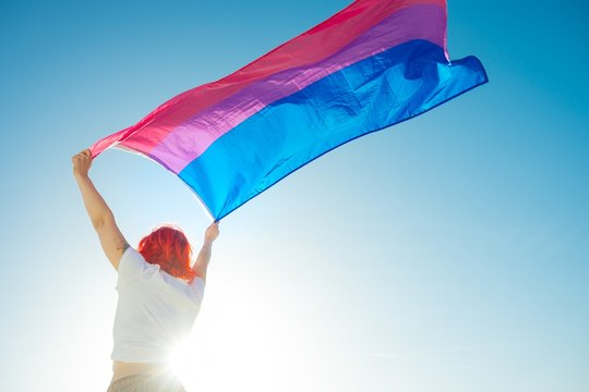 Beautiful low angle shot of a female waving red and blue flag