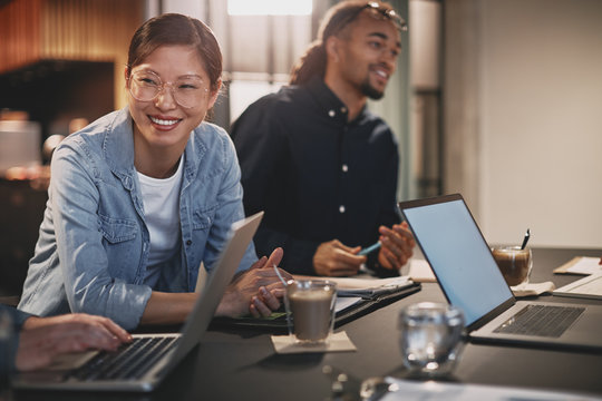 Diverse businesspeople smiling while working with colleagues in