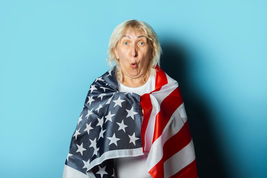 Old woman holds US flag on a blue background. Independence Day celebration concept, memorial day, emigration