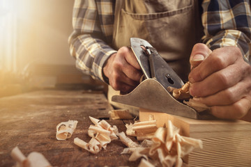 Hands of a carpenter are working with a planer