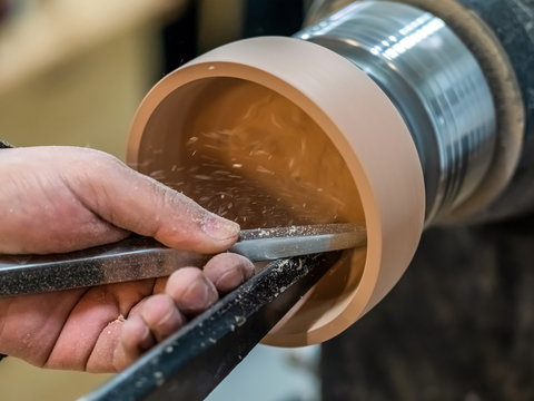Carpenter man is shaving the wooden bowl. Spinning wood wheel. Carving inside forming a round detail. Joiner is using metal tool to make the handmade pot at workshop. Hand is polishing surface.
